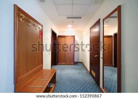Beautiful hallway with wooden closet, mirror and blue carpet. - stock photo