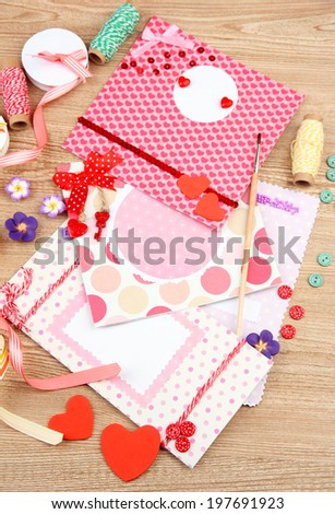 Beautiful hand made post cards and scrapbooking elements, on wooden table - stock photo