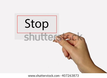 Beautiful hand of a young girl holding a card on a white background with the words Stop - stock photo