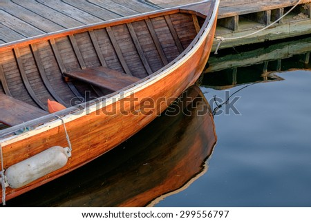 Beautiful handcrafted rowboat and reflection at sunset in a calm harbor - stock photo