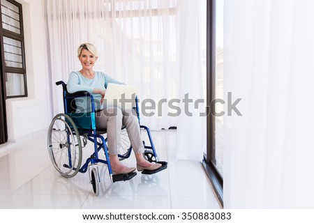 beautiful handicapped senior woman using laptop computer at home - stock photo