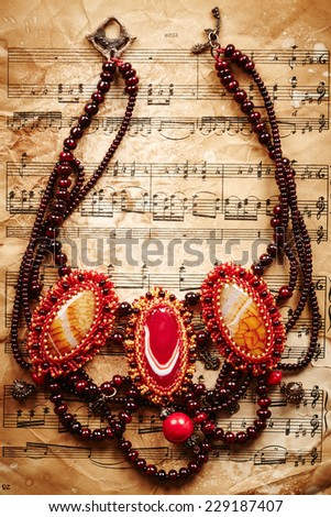 Beautiful handmade necklace on vintage paper background - stock photo
