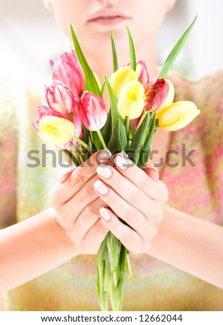 Beautiful hands with French manicure and bunch of tulips. Soft-focused, low DOF - stock photo