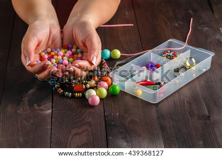 Beautiful hands with perfect nail manicure and colored decorative beads - stock photo