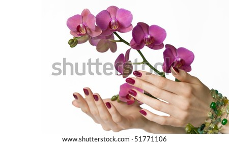 Beautiful hands with pink manicure, green beads touching orchid - stock photo