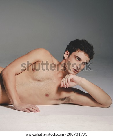 Beautiful (handsome) muscular male model lying down in studio - stock photo