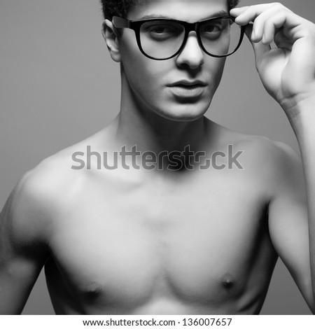 Beautiful (handsome) muscular male model with nice body wearing trendy glasses and posing over light-gray background. Hipster style. Close up. Black and white (monochrome) studio portrait. - stock photo