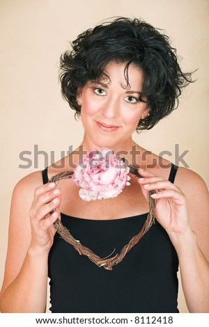 Beautiful happy adult woman  with black curly hair and soft natural make-up, holding a twig heart wreath with pink peony - stock photo