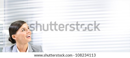 Beautiful happy and smiling business woman at her office and looking right from the camera. Lots of copyspace - stock photo
