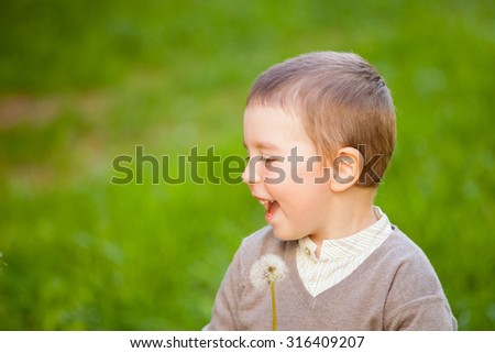 beautiful happy baby boy with blowball, outdoors shoot - stock photo