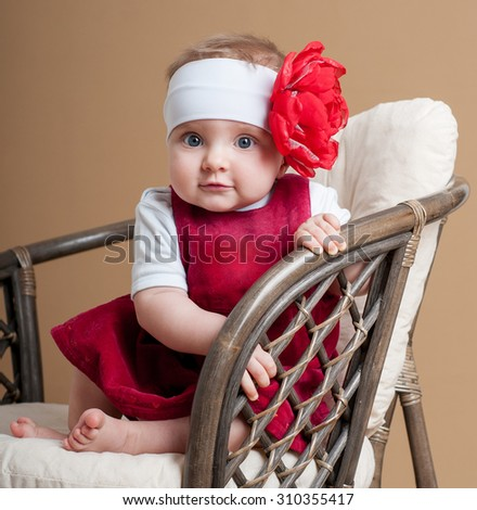 Beautiful happy baby in a red dress. Baby girl. - stock photo