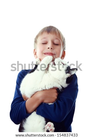 Beautiful happy blond boy embracing a big black and white cat with his eyes closed (isolated on white background) - stock photo