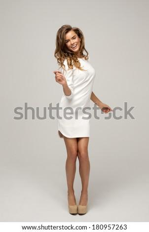 Beautiful happy blond woman in white dress - stock photo