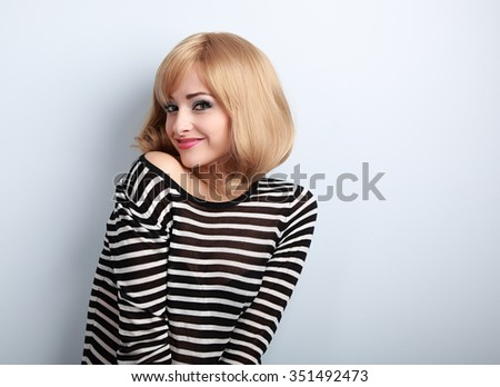 Beautiful happy blond woman with short hair style posing and looking with smile on blue background - stock photo