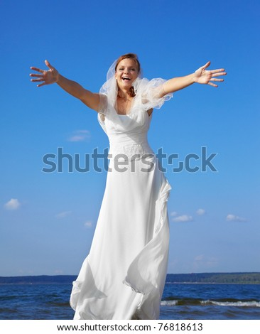 beautiful happy bride standing on stepladder and opening her hands for embrace. blue sky and sea on backround. - stock photo