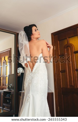 Beautiful happy bride with wedding hairstyle bright makeup in bridal day in love. Happy sexy girl waiting for groom. Romantic lady beauty model bride in bridal day have final preparation for wedding - stock photo