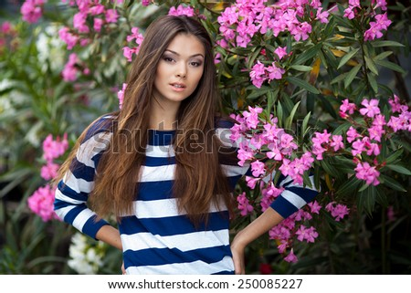 beautiful happy brunette woman in the park against the background of flowers in warm summer day - stock photo