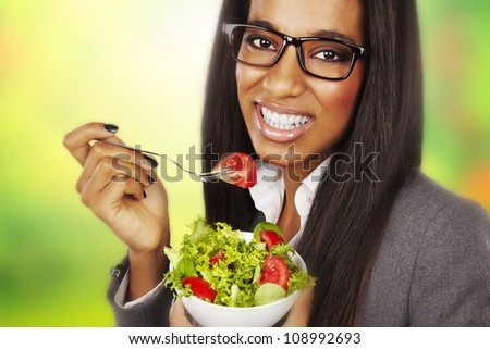 beautiful happy businesswoman eating salad over green background - stock photo