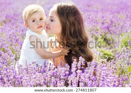 Beautiful happy couple mother and her small cute daughter playing in lavender field on beautiful summer day - stock photo