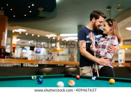 Beautiful happy couple playing billiards - stock photo
