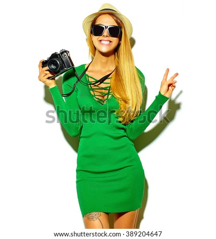 beautiful happy cute blond woman girl in casual summer green hipster clothes takes photos holding retro photographic camera, isolated on a white in hat showing peace sign - stock photo