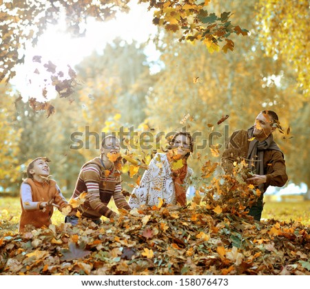 beautiful happy family relaxing in the the park during autumn - stock photo