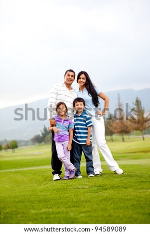 Beautiful happy family standing outdoors and smiling - stock photo