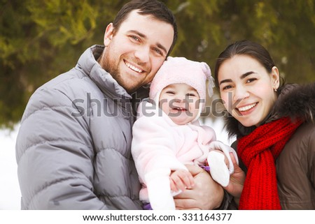 Beautiful happy family wearing warm clothes in winter park - stock photo