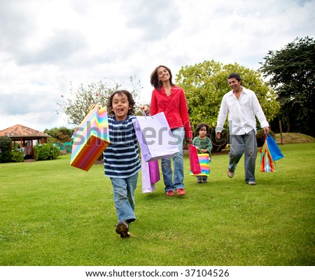 Beautiful happy family with shopping bags outdoors - stock photo