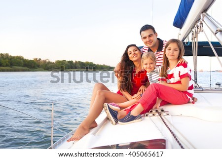 Beautiful happy family with two daughters having great time at the yacht at summertime. Travel and vacation concept - stock photo