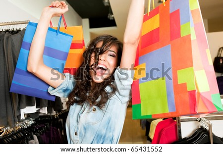 Beautiful happy female in store raising colourful shopping bags with excitement - stock photo