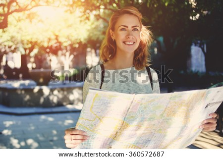 Beautiful happy female tourist exploring location map before touring in a city during her travel, young female traveler with cute smile studying new way on atlas during amazing summer adventure - stock photo