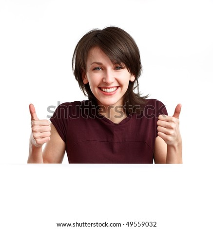beautiful, happy girl behind an empty sheet of paper showing OK with both hands - stock photo