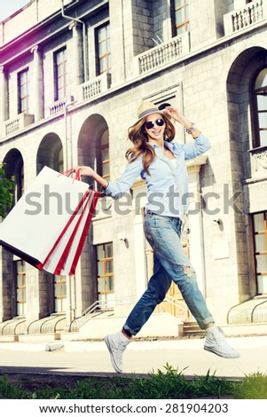 Beautiful happy girl goes shopping in the city. - stock photo