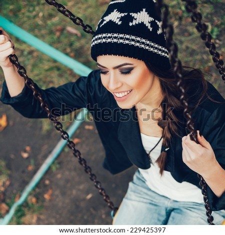 beautiful happy girl hipster on a swing. Outdoors. - stock photo