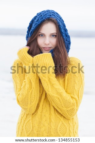 beautiful happy girl in yellow pulloverand blue scarf - stock photo