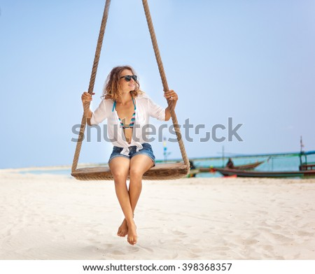 Beautiful happy girl on a swing on the beach. Holiday, vacation, travel - stock photo