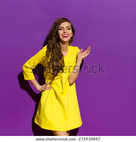 Beautiful happy girl posing in yellow mini dress. Three quarter length studio shot on violet background. - stock photo