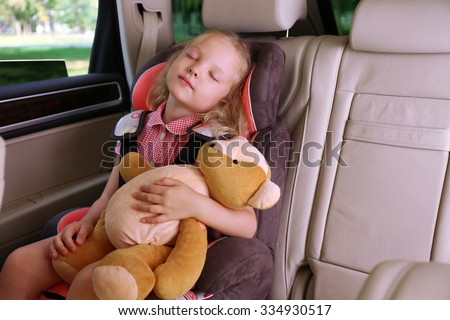 Beautiful happy girl with teddy bear sleeping in the car - stock photo