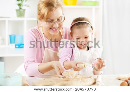 Beautiful happy grandmother and granddaughter Baking in the Kitchen.  - stock photo