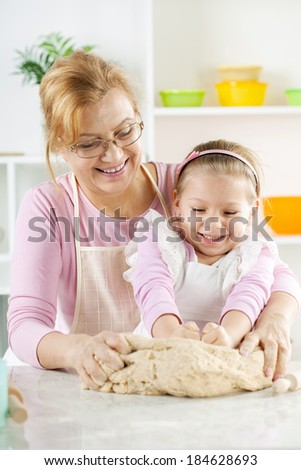 Beautiful, happy grandmother and granddaughter knead the dough together in the Kitchen.  - stock photo