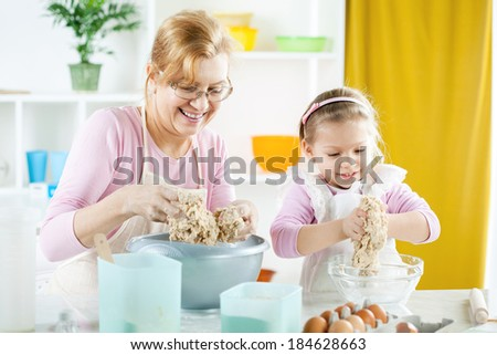 Beautiful happy grandmother learning her granddaughter how making Dough in the kitchen. - stock photo