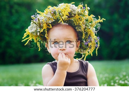 Beautiful happy little baby girl in a wreath on a meadow on the nature in the park - stock photo