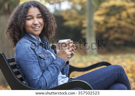 Beautiful happy mixed race African American girl teenager female young woman smiling and drinking takeaway coffee outside sitting on a park bench in autumn or fall - stock photo