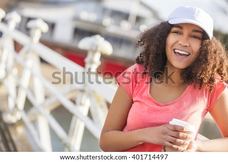 Beautiful happy mixed race African American girl teenager female young woman with perfect teeth smiling drinking takeaway coffee outside wearing white baseball cap and pink t-shirt - stock photo