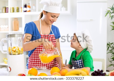 Beautiful happy mother pour orange juice to her child boy in kitchen - stock photo