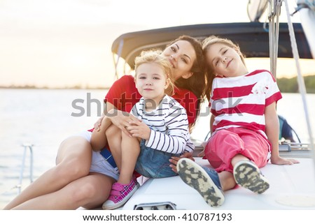 Beautiful happy mother with two daughters having great time at the yacht at summertime. Travel and vacation concept - stock photo