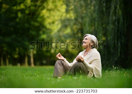 Beautiful happy old woman sitting in the autumn park - stock photo