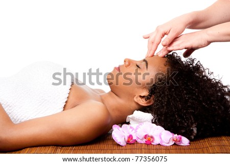 Beautiful happy peaceful sleeping Brazilian woman at day spa, laying on bamboo massage table with head on pillow wearing a towel getting a facial massage, isolated. - stock photo