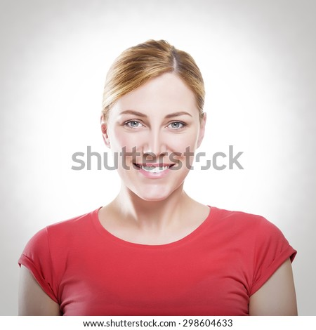 Beautiful happy portrait of an young adult blonde woman in red t-shirt. Toned photo. - stock photo